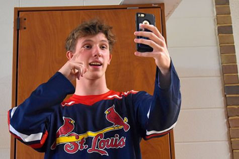 "Standing in the hallways, sophomore Kyle Norman makes a Tik Tok video for his fans. Over the month of September, Norman gained over 2,000 fans on the app. ""Sometimes, I feel like people don't understand what I do or why I do [it] because I get weird looks when I make Tik Toks,"" Norman said. ""Nobody really thinks that it's possible for just a normal guy like me to be so popular without showing it off to everybody."""