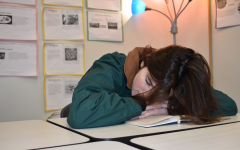 "A student accidentally falls asleep on her book in class. She got two hours of sleep the previous night. ""I always fall asleep in my classes and miss out on information, so then I have to stay up the next night trying to figure out how to do the homework,"" she said. ""This cycle makes everything so hard, but I refuse to sleep at night because hashtag sleep is for the weak."""