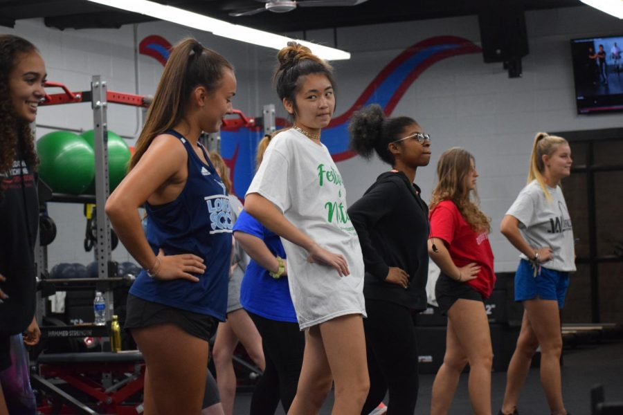 """Seniors Anika Zepeda and Charlize Chiu dance with their classmates while listening to the music play. Students learned 'the wobble' on day one of Movement to Music. """"We learned different types of movement, like dancing styles, but the biggest thing that the teacher is trying to get people to learn is that you don't have to be insecure in that class, and you can take a break from social cues that are in school, have fun [and] move around and be yourself,"""" Zepada said."""
