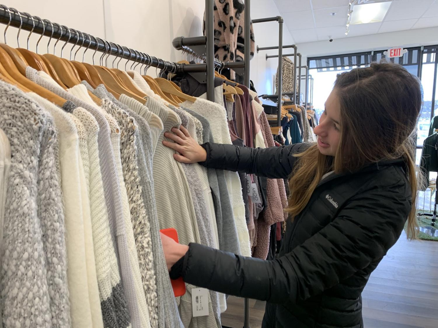"Browsing through racks, LOCO senior class representative Emily Lofgren shops for a new sweater at Mod On Trend. Lofgren helped organize the fundraiser and spread the word on social media. ""I was so excited to hear that LOCO was holding a fundraiser with Mod,"" Lofgren said. ""I get to shop at one of my favorite stores while also contributing to an amazing cause."""