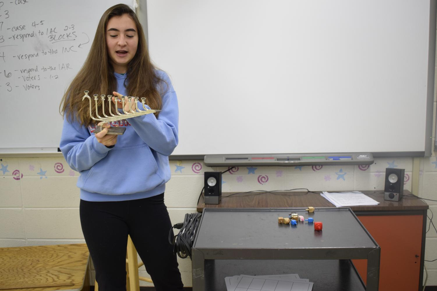 "Pointing to the fourth branch on the Chanukiah, junior Ella Seigel describes Chanukah and other Jewish holidays to her peers. Seigel presented with props to share part of the Jewish culture with students at Westminster. ""Their engagement showed that if you open up and show your differences, that can also provide unity in understanding,"" Seigel said."