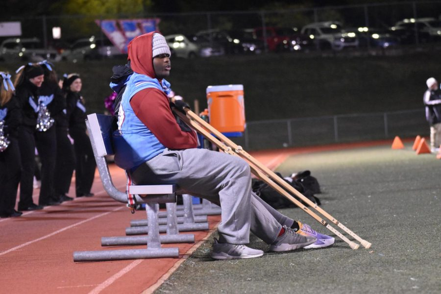 Junior Tim Nelson sitting on the sidelines during the  varsity football game while watching and supporting his           teammates.
