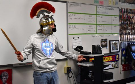 "Latin teacher Tom Herpel entertains students with a sword and a gladiator helmet. In class, Herpel focused on the learning process while making the class enjoyable for students and involving cultural experiences. ""I'll always remember the vocative tense, or command tense, because we learned it and vocab by doing yoga-like the game Twister,"" Rutledge said."