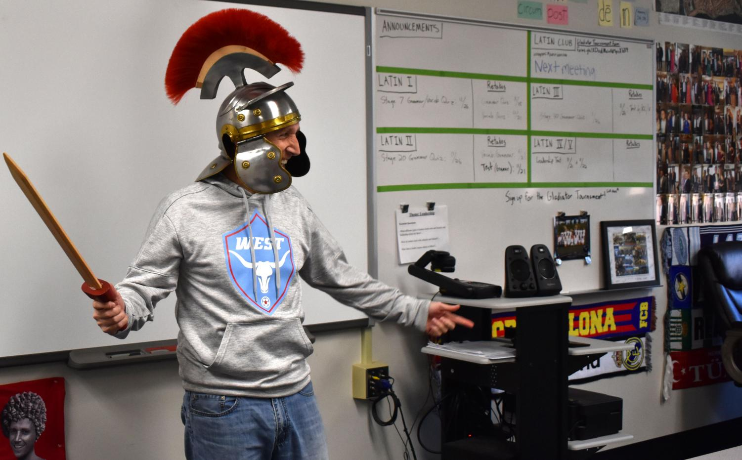"""Latin teacher Tom Herpel entertains students with a sword and a gladiator helmet. In class, Herpel focused on the learning process while making the class enjoyable for students and involving cultural experiences. """"I'll always remember the vocative tense, or command tense, because we learned it and vocab by doing yoga-like the game Twister,"""" Rutledge said."""