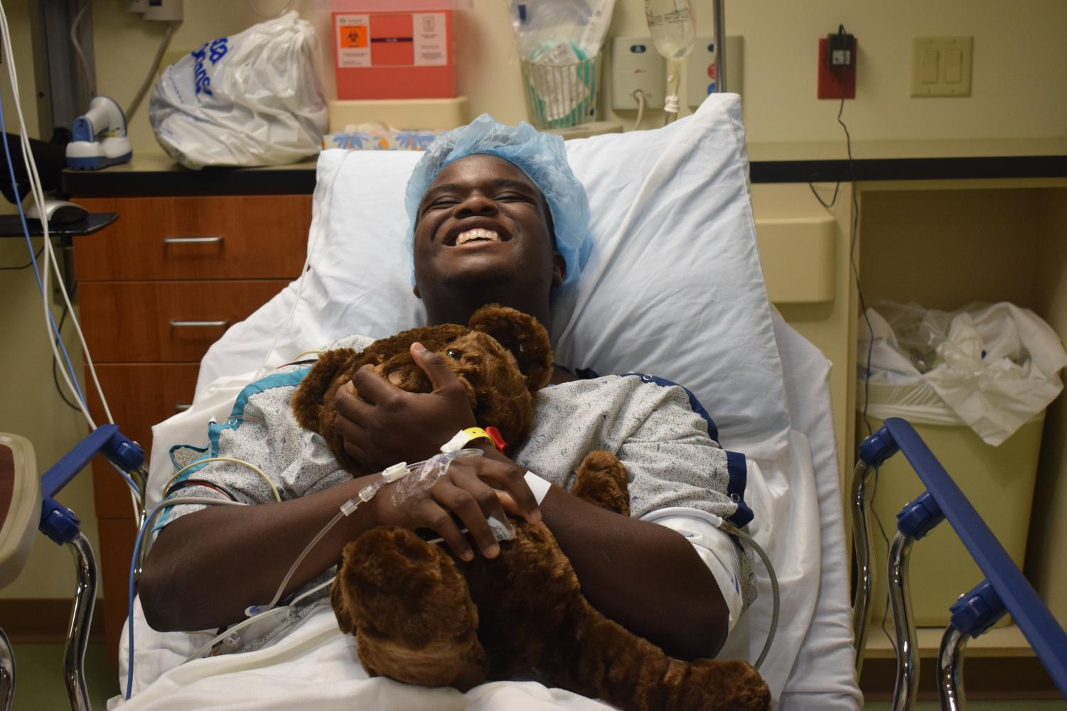 """Smiling before surgery, junior Tim Nelson holds a teddy bear. Nelson was excited to undergo surgery so that he could begin the long recovery process. """"After the pain goes away, I know [the  recovery process] will be easy,"""" Nelson said. """"I just need to have patience, and that's kind of something I don't have all the time."""""""