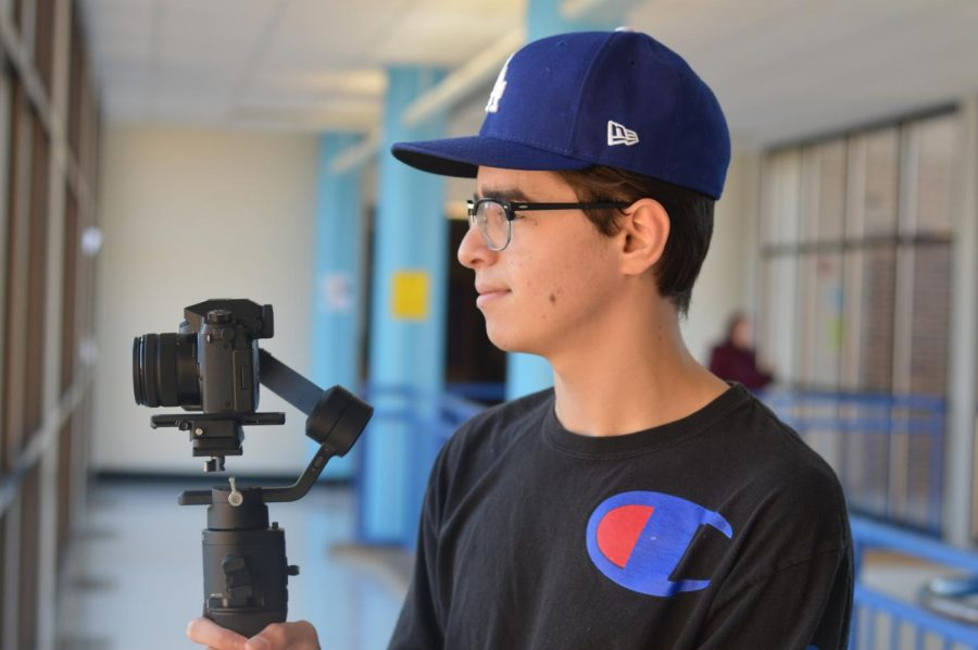 "Senior Ismail Hacking focuses his camera using his stabilizer. Hacking has invested in high grade video equipment to better the quality of his videos. ""Video is unlike any other art form in the way that it combines visuals with audio to create something that speaks to people,"" Hacking said."