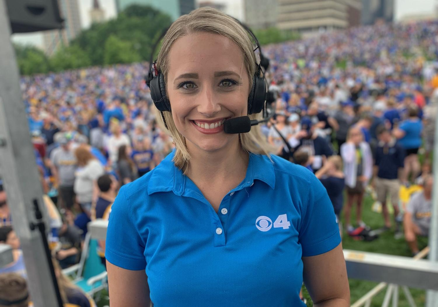 """Standing on The Arch grounds, Kim St. Onge covers the St. Louis Blues rally after winning the Stanley Cup. St. Onge wore a headset to hear the anchors in her ear. """"The crowd was so loud that day that even with the headset I could barely hear the show. I was on a stage in the middle of tens of thousands of people–pretty surreal! It was so cool to see the whole city come together to support the Blues. I'll forever think of that day as one of the coolest things I've ever done,"""" St. Onge said."""