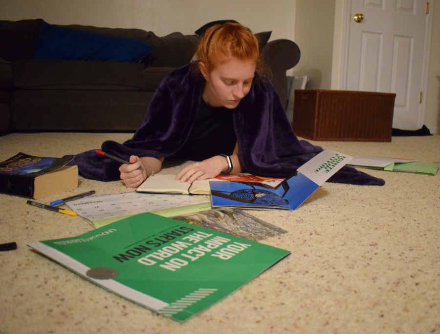 """2019 alumna Nell Jaskowiak looks over college brochures, weighing the benefits and drawbacks of each school. Jaskowiak plans to attend a state school in the fall. """"I feel like so many kids take college for granted,"""" Jaskowiak said. """"I think kids don't realize how amazing it is to pick good schools to apply for and have good choices to choose from."""""""