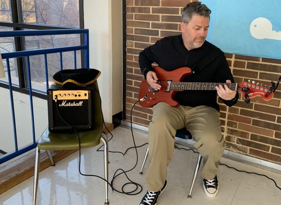"""History teacher Mel Trotier plays his guitar during the passing period to collect donations for the anual Social Studies Department  canned food drive. Trotier began this tradition four years ago, to bring awareness to the fundraiser and raise money. """"Even in a wealthy community, there's still so many families that don't have money to even eat through the holidays,"""" Trotier said. """"I think it's an important issue to bring up to kids that may not realize that somebody sitting in the classroom with them needs food."""""""