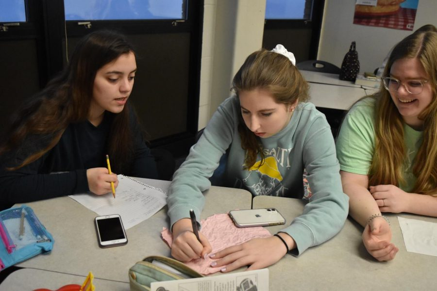 Continuing their story, juniors Emma Pence, Chloe Stillman and Ruthie Vierling participate in an activity at a Spanish Club meeting Jan. 24. Club members added one sentence in Spanish before passing the paper onto the next student.
