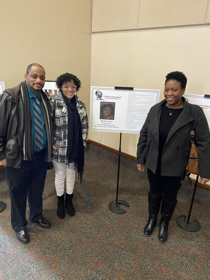 Junior Bri Davis stands with her father Ywain Davis and mother Deandria Davis as she entered the reception. Davis' poem and picture were featured at the enterance.