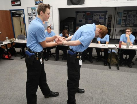 "Perfecting the right way to handcuff someone, junior Jake Braymiller learns  how to be a police officer. This is Braymiller's first year attending the program, but he plans to continue next year. ""This program really helps you get career ready for whatever it is that you want to pursue, and it's really cool how they train you and get you ready for what's coming after you graduate,"" Braymiller said."