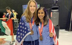 "Wrapped in the American flag, senior Erin Slutzky and doubles partner, freshman at University of California, Berkeley, Nikita Chauhan celebrate their performance at the International Racquetball Championships (Worlds). Though this was Slutzky's second Worlds debut, she won a medal for the first time. ""The best thing about getting bronze was the improvement it showed from the year before at Worlds in Mexico where I didn't get a medal. It meant my hours and hours of training had paid off,"" Slutzky said."