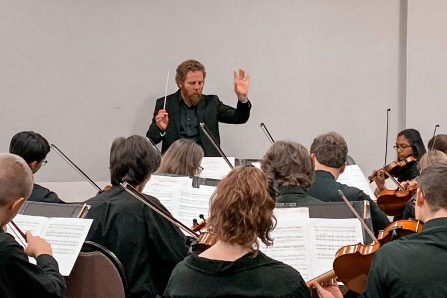 """Thirty minutes before the concert at the Missouri Music Educators Association (MMEA) workshop conference, members of Symphonic Orchestra rehearse """"Libertango"""" under the direction of orchestra teacher Ed Sandheinrich Jan. 24. Throughout the three-day workshop, performance groups were given half an hour to tune, warm up and wrap up the final details before their performance. """"Everyone was awesome in their playing and their professional behavior. It was hard for me to go from point A to point B at the resort because, well, it's a crowded mess, but people kept stopping me to say how much they loved the performance,"""" Sandheinrich said."""