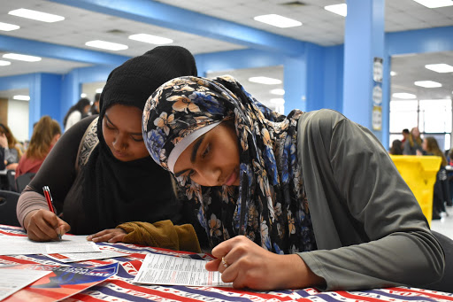 "Filling out the information on the registration form, seniors Fariha Hossain and Muneebah Qayyum register to vote at the voter registration drive. The Feminist Club, with the League of Women Voters held the event Wednesday, Jan. 29 and registered 73 students. ""If you have an option to vote and support something, you should,"" senior Fariha Hossain said. ""You can use your voice to help people."""