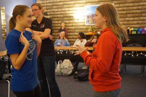 "Freshmen Elle Rotter and Sami Eveland have a conversation during ASL club's Friendsgiving meeting. The club had pizza and soda while chatting and playing games. ""I enjoy visiting ASL club and talking to my friends,"" Eveland said. ""I've met some cool new people who are interested in ASL just like me."""
