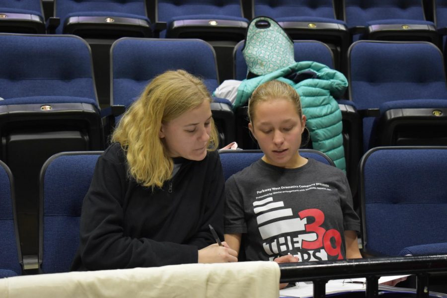 Junior Clementine Arneson and senior Emma Whittenburg write down blocking notes.