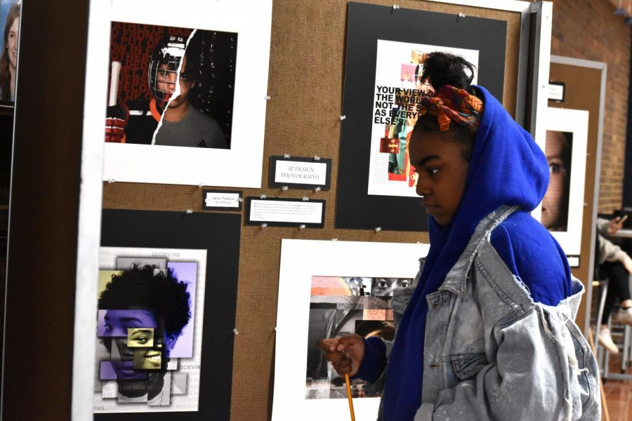 "Searching for the piece of art that she will respond to, Creative Writing student and senior Allainah Crawford looks at works from the AP Design and Photography class. ""This project is 'free range' compared to some of the other ones,"" English teacher Dan Barnes said. ""With express the music, we have word count, [but] with this one, I just want my students to be inspired by art."""