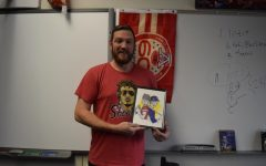 "Holding a Kansas City sports themed picture, English teacher Casey Holland displays his classroom adorned with Chiefs decor. Holland will watch his favorite NFL team compete in the Super Bowl for the first time in his life Feb. 2. ""I was born and raised a Chiefs fan. I'm from Southwest Missouri two hours south of Kansas City. My friends and I in elementary school all liked the Chiefs and our parents liked the Chiefs and we used to go to games all the time. I was just born into it."