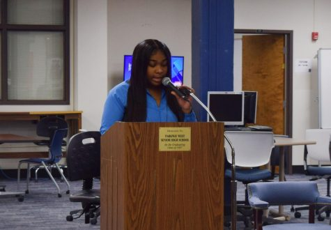 Performing an original piece, senior Taylor Fischer raps for students attending the African American Read-In in the library.