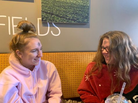 "Juniors Bella Allgeyer and Reese Berry laugh over breakfast before heading to class. The two attended the Ash Wednesday mass at Incarnate Word Parish 7 a.m. to celebrate the beginning of the Lenten season. ""It's something that is kind of a necessity to us, that we sacrifice to show that other things are more important,"" Allgeyer said."