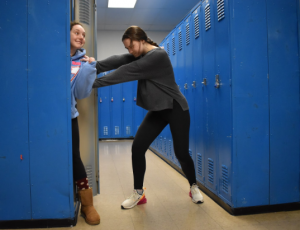 "Junior Ima Dropout tries to escape as senior Betsy Class tries to put her into a locker. Since joining the school last year, Dropout has faced adversity with honors students bullying. ""When I first came here I was hoping it would be a little different from [Parkway] South. Turns out I was so unbelievably wrong,"" Dropout said. ""Everyone at this school is way bigger, stronger and smarter than back at my old school, and it honestly scares me."""