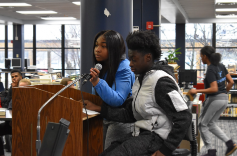 "Speaking into the microphone, senior Taylor Fisher reads a poem written by the African American Literature class. Fisher emphasized her cultural pride. ""We love our skin, and we love what we do. We're very powerful,"" Fisher said."