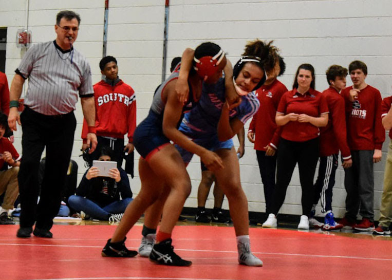"""As the spectators on the side look on, junior Faith Woodall attempts to get the upper hand on her female opponent. Woodall is a first-year wrestler, joining after the girls wrestling team began to gain traction. """"I really like it because they support each other in their endeavors and the team is just really close,"""" Woodall said."""