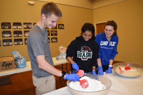 "Volunteering at the United Hebrew Congregation Challah Club, seniors Jonah Yates, Anjali Shah and Emma Caplinger dispense flour to participants. Due to coronavirus fears, there was an equal amount of participants as there were volunteers. ""The most rewarding aspect of the volunteer opp was that I was able to connect not only with West volunteers but the Jewish community and do an activity that I"