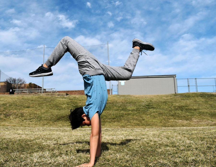 "Freshman Tristan Caudill practices a handstand in a field.  Caudill pushed to try new things even when they seemed intimidating. ""My coaches always tell me 'get comfortable with being uncomfortable,'"" Caudill said. ""A lot of what you're going to do is stuff that you will not be comfortable with, but if you don't get comfortable with that, you're not going to progress at all."