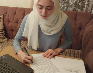 "Annotating her copy of the short story, sophomore Zeina Daboul works on her assignment. Daboul found the parallels between the story and modern times interesting. ""When you look deeper [into the story], you can see that it reflects our society, in ways that you wouldn't think a story written in 1842 would,"" Daboul said."