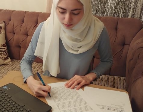 "Annotating her copy of the short story, sophomore Zeina Daboul works on her assignment. Daboul found the parallels between the story and modern times interesting. ""When you look deeper [into the story], you can see that it reflects our society, in ways that you wouldn"