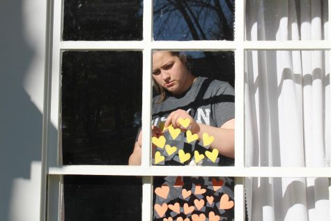 "Sister of senior Madi Foppe, Kennedy Foppe, tapes paper hearts to her window to form a rainbow of hearts. She came up with the idea after seeing people share rainbows and wanted to incorporate hearts to represent love and kindness for healthcare and essential workers. ""We enjoy [art] but we don't get to do it a lot. During quarantine we have definitely gotten to do more,"" M. Foppe said. ""We had an idea to create a rainbow of hope out of hearts to spread hope and love during these uncertain times."""