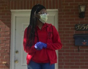 Preparing to go to her job as a bagger at Schnucks, Davis puts on her face mask and gloves. While most students are staying home, Davis goes out each day as an essential worker.