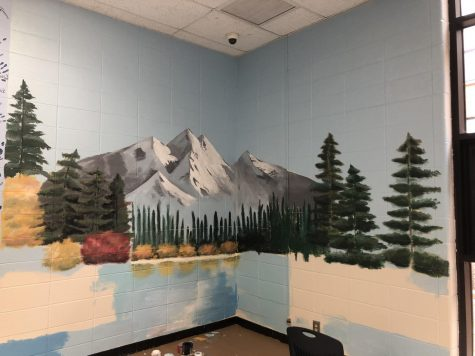 """Students gather to paint the senior wall, which is Bob Ross themed this year. Seniors Lauren Beard and Chloe Narishkin designed the wall and now have to adjust to the school closing. """"I think it's cool to have that kind of impact and see that what I thought of was on the wall, I wanted it to be something really fun,"""" Beard said."""