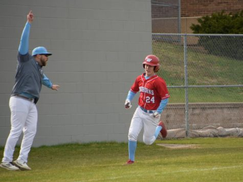 """Junior varsity baseball coach Andrew Jett swings his arms while coaching third base telling senior Jason Reilly to run to home plate.  Jett feels at home when coaching baseball. """" I hope that in 10 years I meant so much to them that they invite me to their weddings,"""" Jett said."""