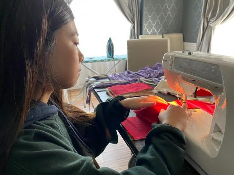"Sewing two layers of a mask together, freshman Hannah Choi creates masks to donate to BJC hospital, the police department and nursing homes. Choi's neighbor gave her the idea to donate masks to first responders. ""This is the first time I've ever sewn, so it's new to me, but sewing is helping me pass time. Once you start, it's kind of addicting, and it takes away my boredom,"" Choi said."