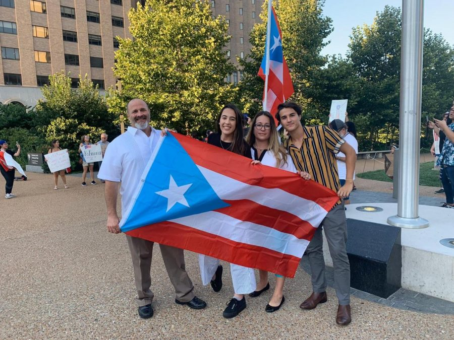 Holding the Puerto Rican flag,  Gonzalez and his parents attend an event in downtown St. Louis with other Puerto Ricans that live in the area.