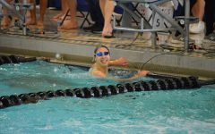 """Senior Lauren Beard finishes her last lap at a swim meet. Beard plans to continue swimming at the collegiate level. """"It's such an escape from life's craziness,"""" Beard said. """"It allows me to take a step back and get out all of the anger and frustration I have built up. The community is so supportive and it's like a second family."""""""