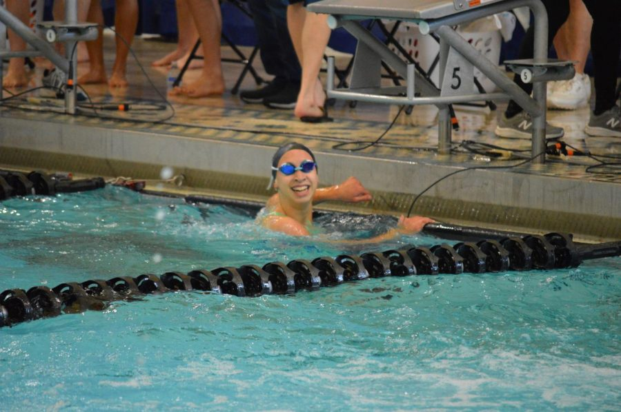"Senior Lauren Beard finishes her last lap at a swim meet. Beard plans to continue swimming at the collegiate level. ""It's such an escape from life's craziness,"" Beard said. ""It allows me to take a step back and get out all of the anger and frustration I have built up. The community is so supportive and it's like a second family."""