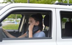 "Using a bandana as a makeshift mask, sophomore Ellie Moriarity adjusts it on her face before she begins to drive. Moriarity believes there is always a risk associated with leaving your house during these uncertain times. ""I think it's important to wear a mask right now because there is no way of knowing if you have contracted the coronavirus,"" Moriarity said. ""It's better to be safe than sorry when it comes to protecting those around you."""