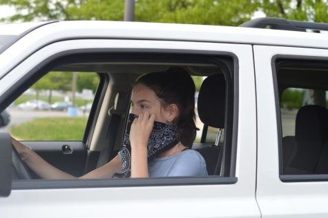 "Using a bandana as a makeshift mask, sophomore Ellie Moriarity adjusts it on her face before she begins to drive. Moriarity believes there is always a risk associated with leaving your house during these uncertain times. ""I think it"