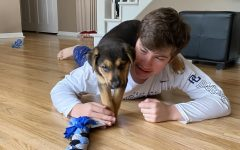 "Taking a break from school work, freshman Tyler Lang relaxes and plays with his new puppy Rona. After adopting the puppy a few weeks ago from Feral Companion, the Lang family named Rona after the Coronavirus. ""I think having a dog during this time is helpful because it's a good break away from eLearning and it also lightens the mood of everyone in our house,"" Lang said."