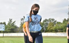 Walking across the field, junior Callie DiCarlo attends softball practice on Sept. 16. The players wore masks during non-strenuous activities and distanced in the dugout.