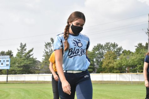"Walking across the field, junior Callie DiCarlo attends softball practice on Sept. 16. The players wore masks during non-strenuous activities and distanced in the dugout. ""It's been hard especially because I feel for the seniors that their season isn't normal, so I've been getting closer with girls on the team and it's been lots of fun,"" DiCarlo said. ""Our practices are definitely different right now due to health precautions."""
