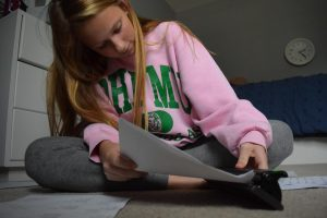"Laying out her papers, freshman Allison VanValkenburgh does her homework. VanValkenburgh is getting used to switching over from paper to digital. ""in normal school we would've had more paper assignments.and I learn and test the best on paper,"" VanValkenburgh said. ""With learning being 90% online, it's hard adjusting to the new norms and expectations."""