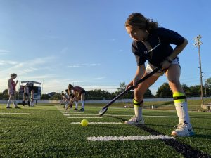 "Working on her ball control, sophomore Lexie Lutz practices with her field hockey team while maintaining distance. With COVID-19 regulations impacting every fall sport, field hockey is considered a moderate frequency sport so they must gradually progress into full contact with one another. ""I am disappointed because playing field hockey is something I look forward to all year, so it's a big letdown to have COVID put restrictions on me and my team because it makes it harder to enjoy,"" Lutz said."