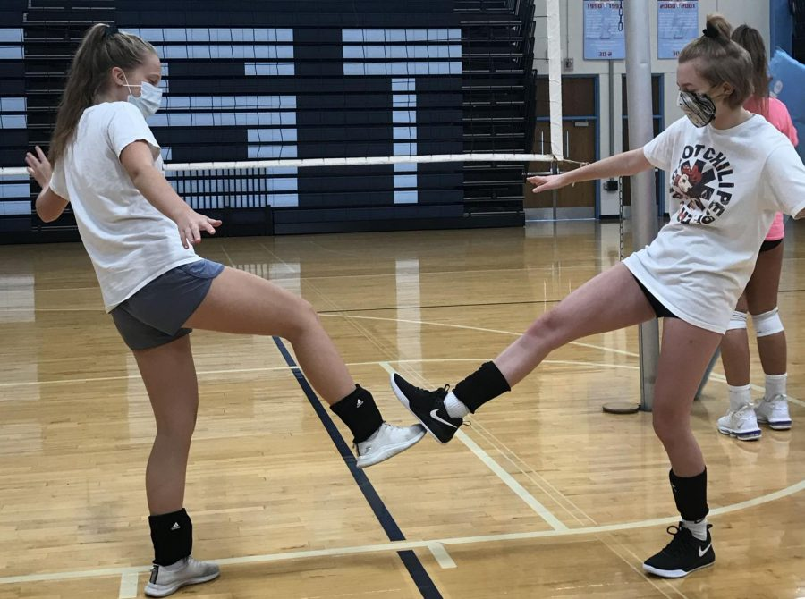 "Cheering each other on, freshmen Cora Tiemieir and Ashley Lewenski use a unique way to celebrate. Due to COVID-19 restrictions, the girls were not allowed to partake in high fives or fist bumps. ""We like to"