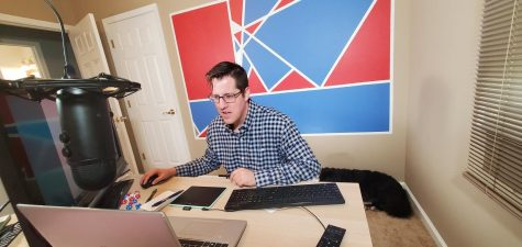 "Working at his virtual teaching setup from home, math teacher Patrick Troy prepares for the day with his Border Collie, Luna, laying behind him. Troy feels there are multiple benefits to teaching on a computer opposed to writing on a whiteboard. ""My setup allows me to work on the computer, instead of writing on a whiteboard or paper behind me,"" Troy said. ""It allows me to directly look at my students while I"