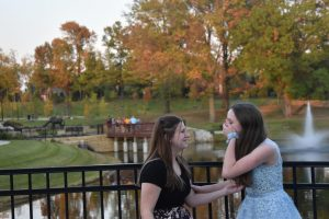 "Wearing dresses at Town and Country Square, sophomores Sami Eveland and Sammi Duncan dress up for their self-created homecoming. Despite COVID-19 cancelling school-sponsored homecoming , Duncan and her friend group decided to plan their own event and make the most out of the situation. ""We were all super bummed about homecoming being cancelled,"" Duncan said. ""We just wanted to have a fun time with our friends whether it was for real or [fake], but we all knew that it was for our safety and getting to plan our own made us feel a lot better."""